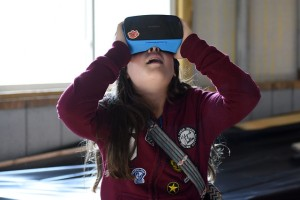 Young girl looks up wearing VR headset.